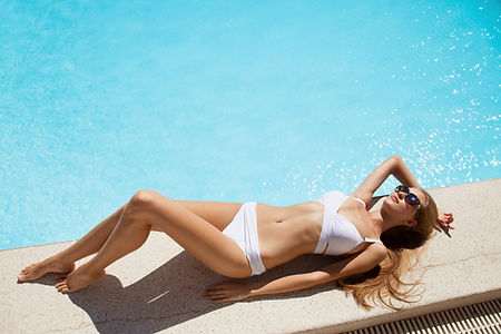 Young woman sunbathing near swimming poo