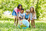 Multicultural group of kids rolls globe