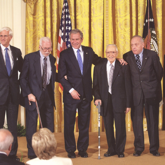 Standing on stage in the East Room of the White House alongside four Monuments Men as President Bush presented the Monuments Men Foundation with the National Humanities Medal. (November 2007)