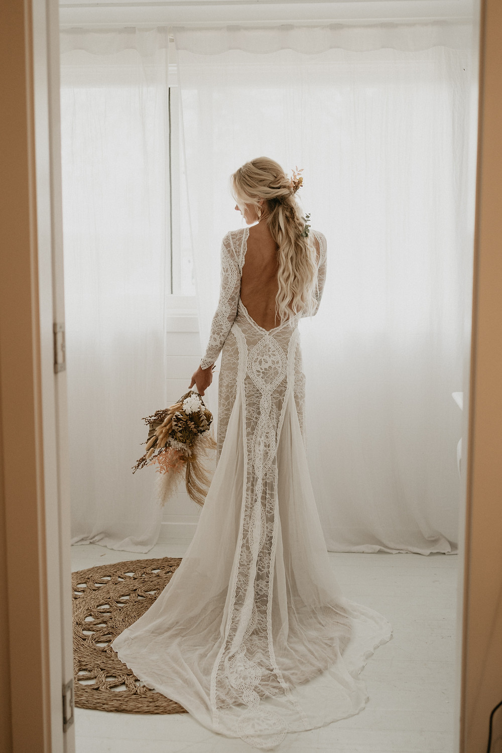 young bride in boho style dress and wedding bouquet