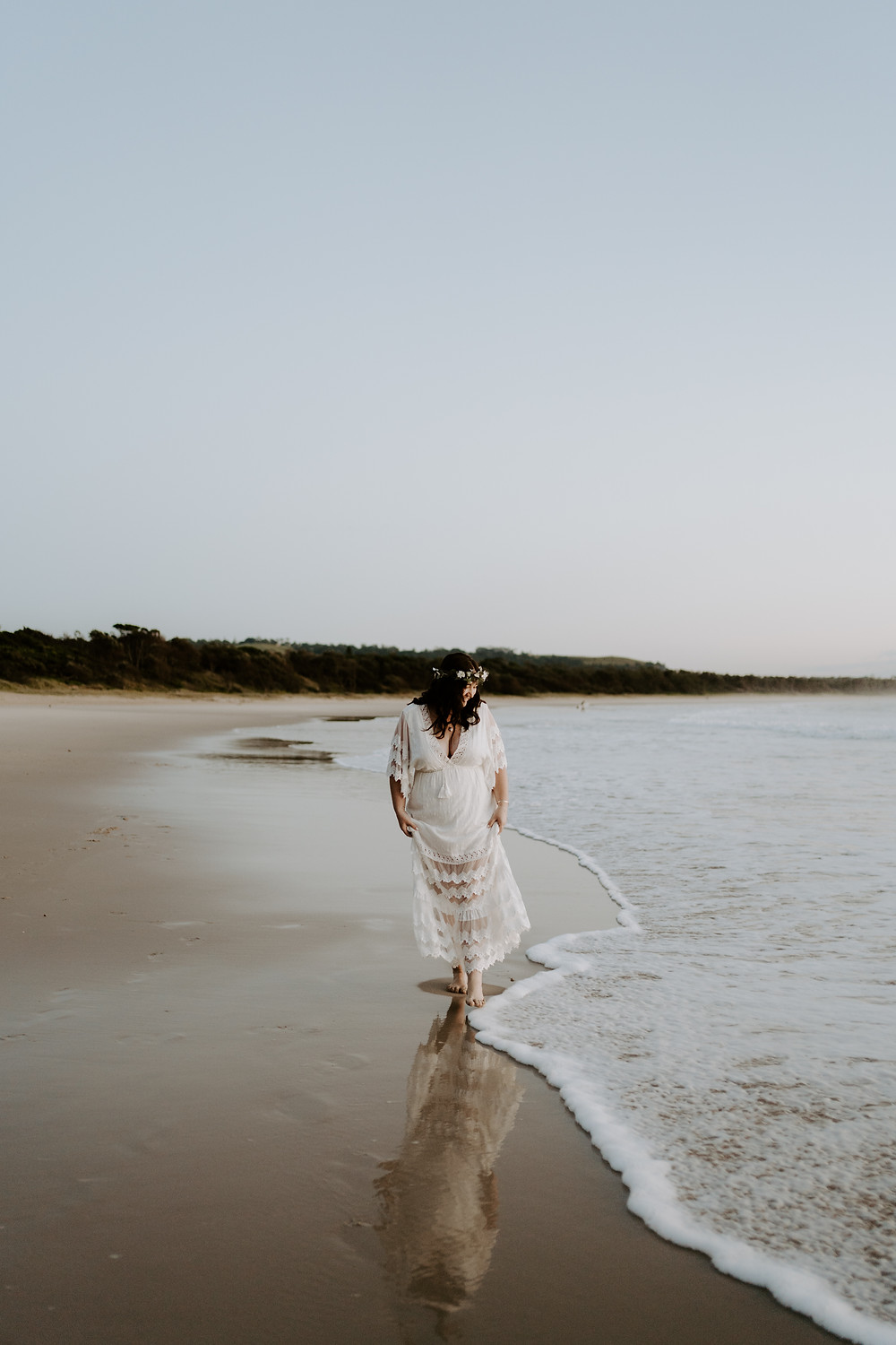 young boho bride walks along Byron bay beach at sunrise before her elopement