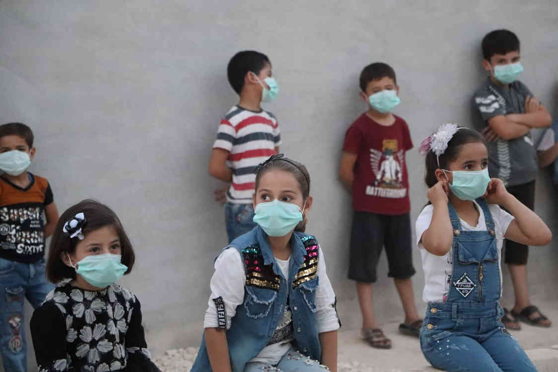 Socially distanced Syrian children await puppet show