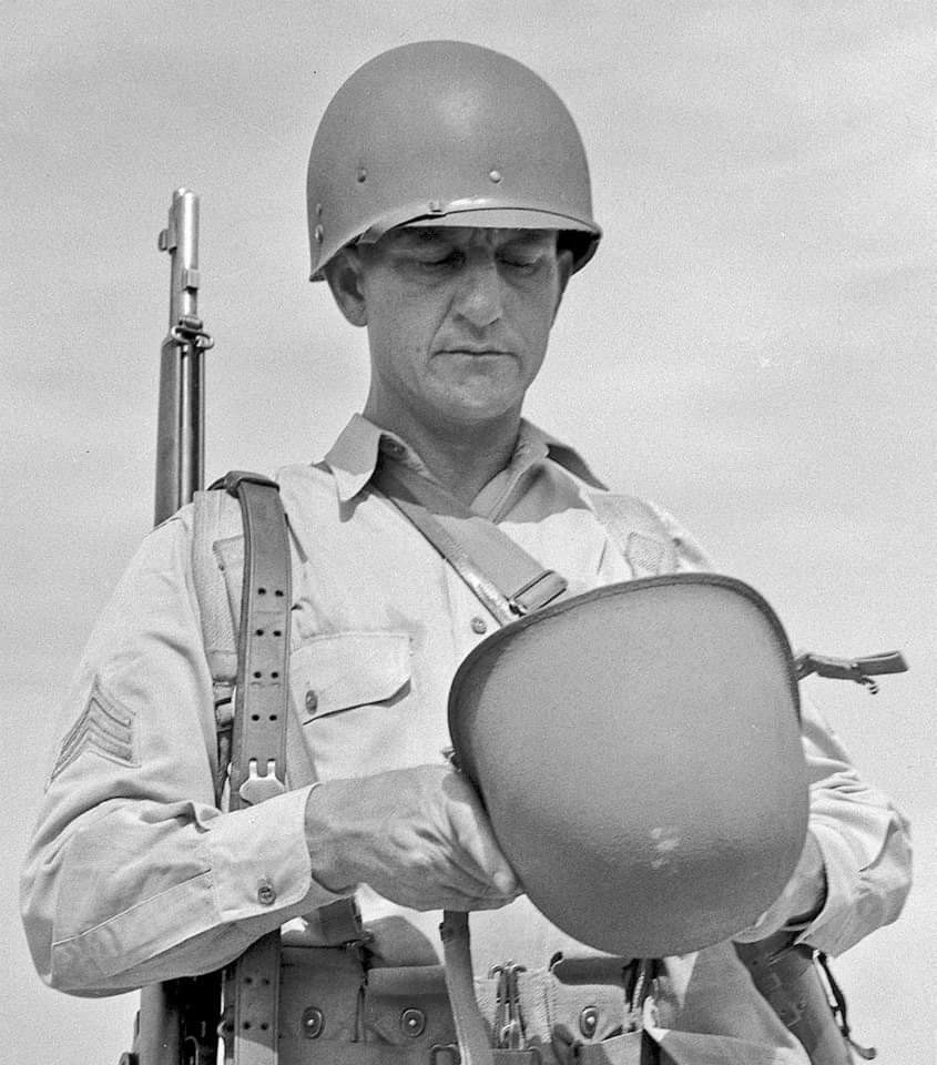 An American serviceman inspecting the new M1 helmet. The liner he is wearing is one of the prototypes produced by Riddell (note the smooth plastic finish and the additional rivet at the side, directly beneath the chinstrap-retaining rivet). August 13, 1941