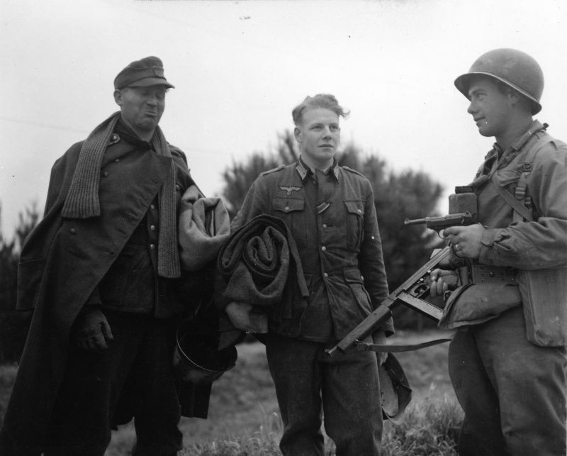 An American soldier with a captured P.38 guards two German prisoners of war.