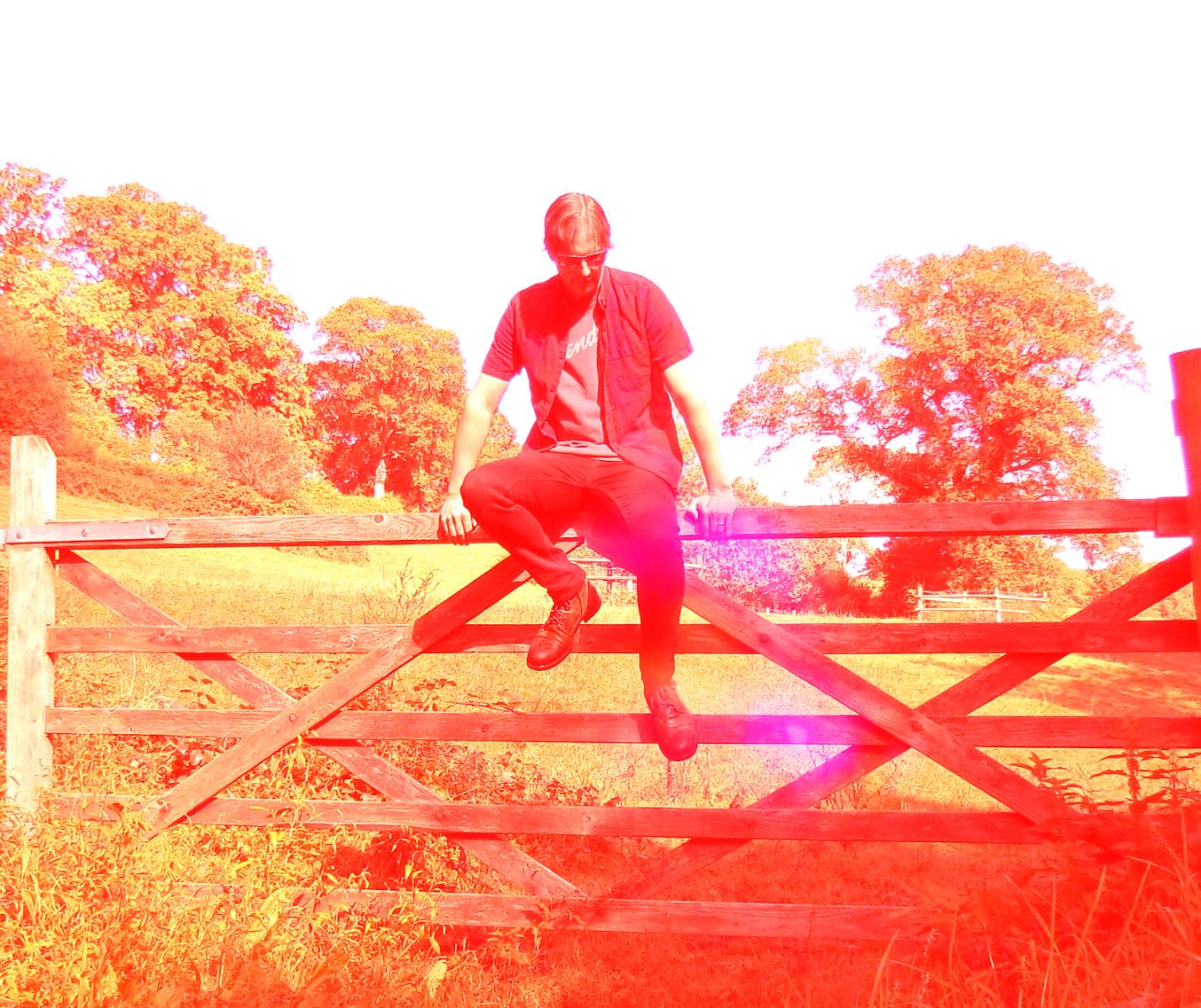 Indigo Daydream-musical-artist-sitting on a gate-Dartington-Devon-daydreaming.png