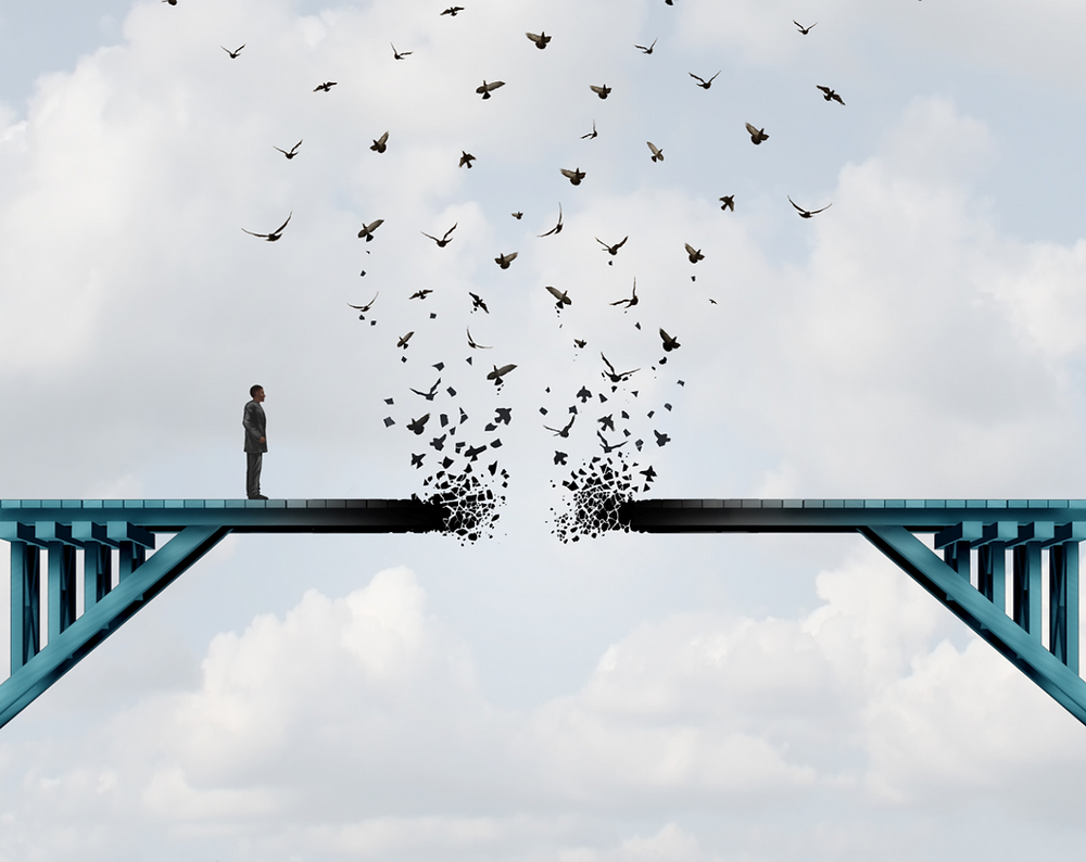Man standing on a bridge. Bridge is breaking ahead into flying birds. Man looking lost.