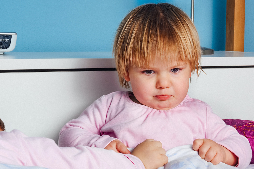 toddler pouting her lips as a sign of anger, and about to burst into tears.