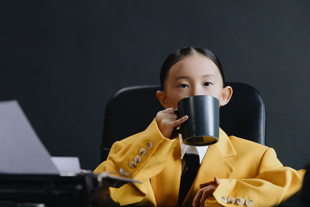 Child in oversized suit sitting at desk drinking from a mug like an adult would