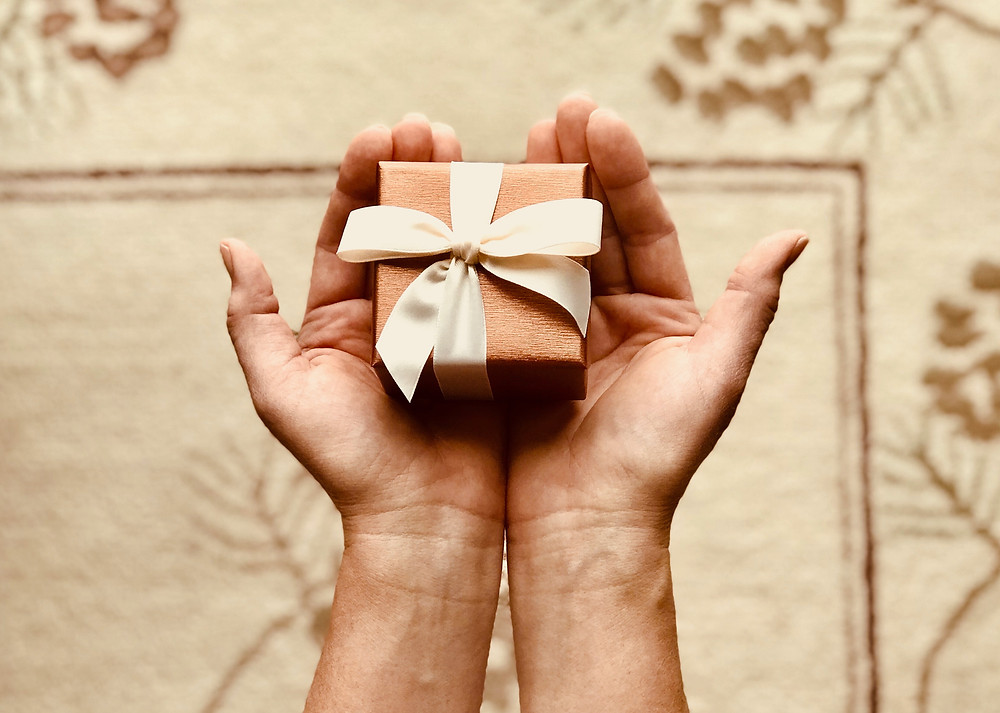 Hands held out with a small gift inside them. Giving a gift.