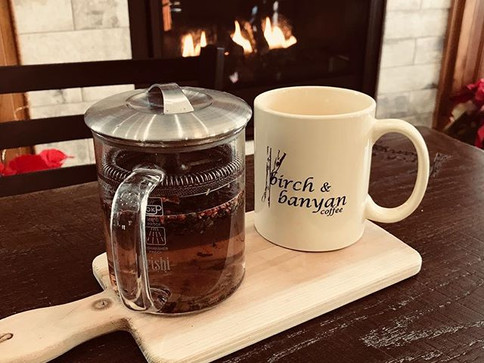 Come cozy up in front of the fire with a delicious cup of _rishitea #birchandbanyancoffee #rishitea #cozy #fireplace #winter #colddaysarefor