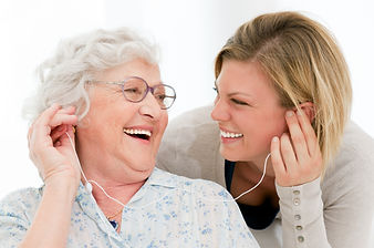 Elderly women listening to music with her caregiver in the comfort of her home in Minneaplis Minnesota in home senior care