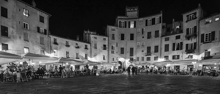 Restaurant with people at night in Lucca, Italy