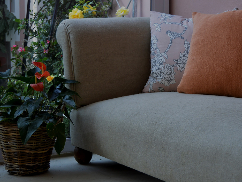 The couch in the natural linen and the cushions in pink and orange.