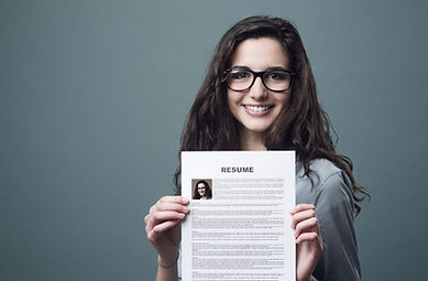 Young women smiling and holding a professionally written resume