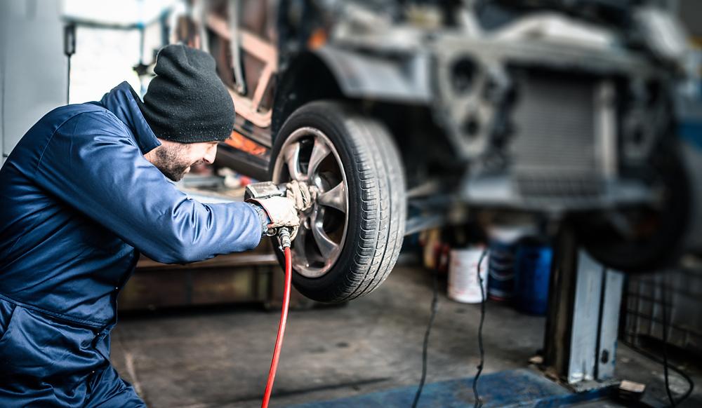 Self-employed mechanic fixing car wheel