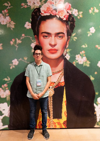 Jason Vega standing in front of portrait of Frida Kahlo