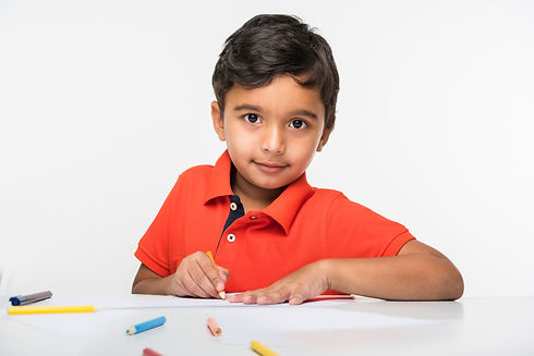 indian-boy-child-using-colourful-pencil-drawing-studying-with-globe-magnifying-glass-sitti