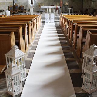 dekoracja kościoła z białym dywanem i latarenkami