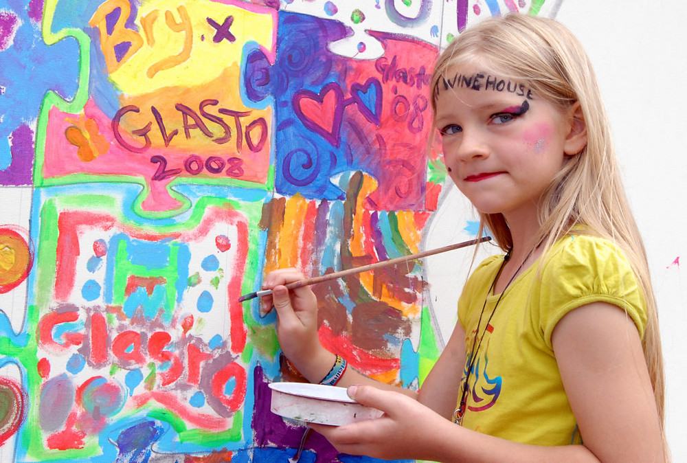 A young girl painting at a local arts festival. Photo: Tabatha Fireman/Redferns/Getty Images.