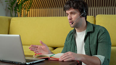 young-man-wearing-headphones-is-sitting-on-a-yellow-sofa-at-home-talking-on-a-video-link-o...top.jpg