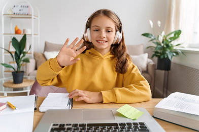 smiling-school-girl-making-video-call-with-laptop-at-home.jpg