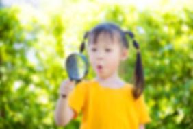 Little asian girl looking thru magnifyin