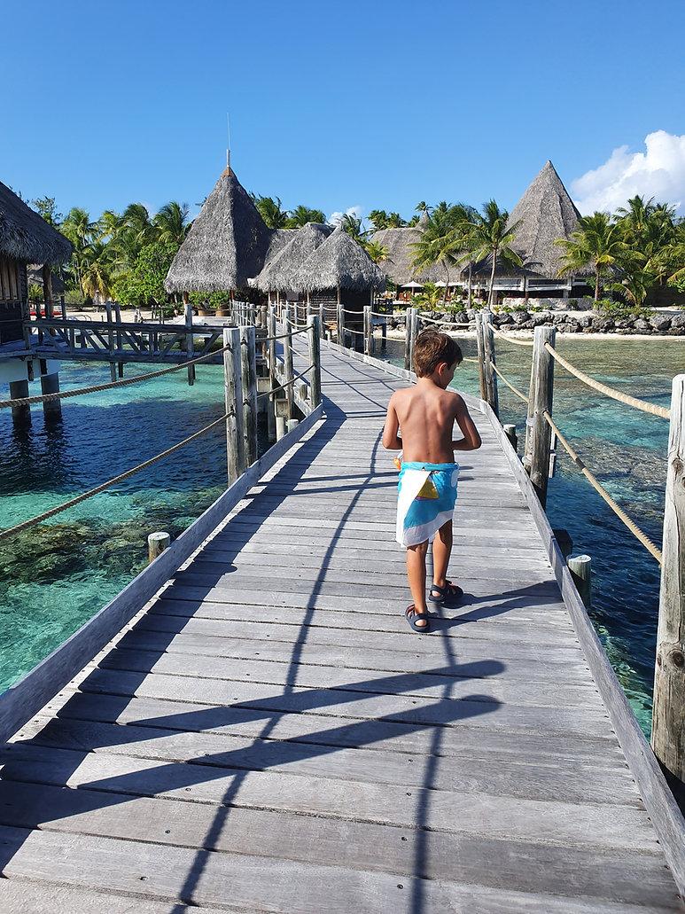 petit garçon en paréo marchant sur des pilotis en Polynésie Française