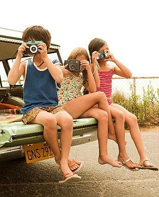 trois enfants en maillot avec appareil-photo