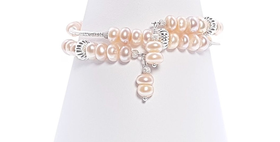 Peach pearls and sterling silver wrap around bracelet on stand