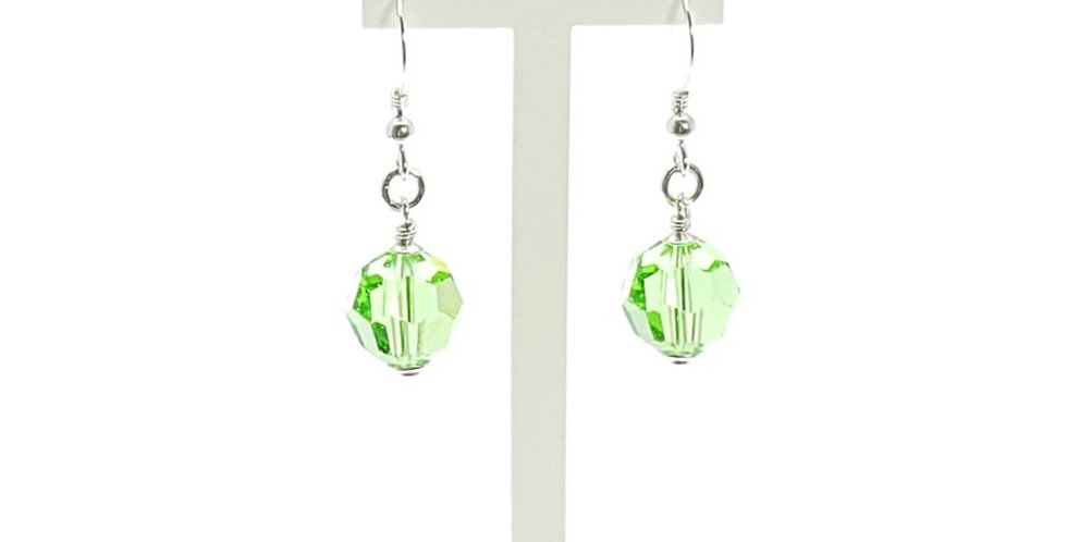 handmade sterling silver earrings with green Swarovski crystals on display stand