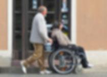 Man Pushing Woman In Wheelchair.
