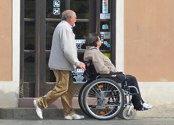 Man Pushing Woman In Wheelchair.