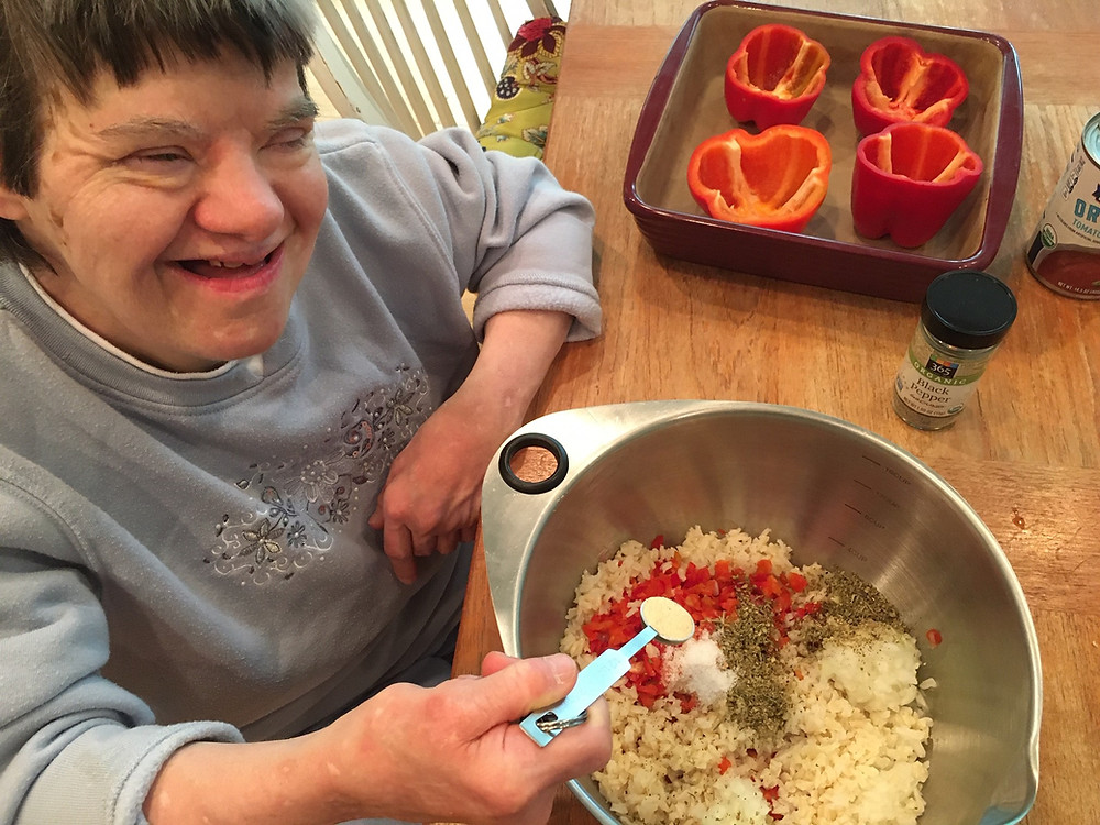 Diane smiles while she adds ingredients for stuffed peppers into a mixing bowl.
