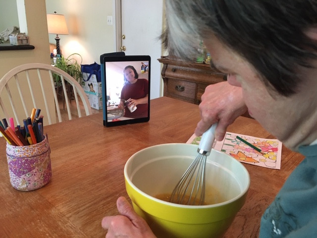 Diane whisking ingredients in a yellow mixing bowl with iPad screen in front of her.