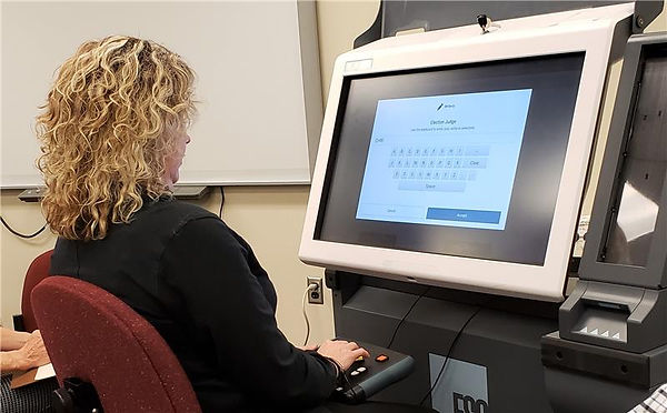 Woman sitting in chair using new voting machine.