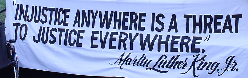 """Banner With Quote From Martin Luther King Jr. Banner Reads """"Injustice Anywhere Is A Threat To Justice EveryWhere."""""""