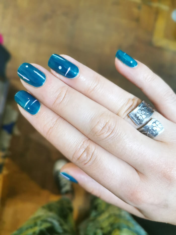 An close up of fingernails that have been painted in teal with dot and line nail art.