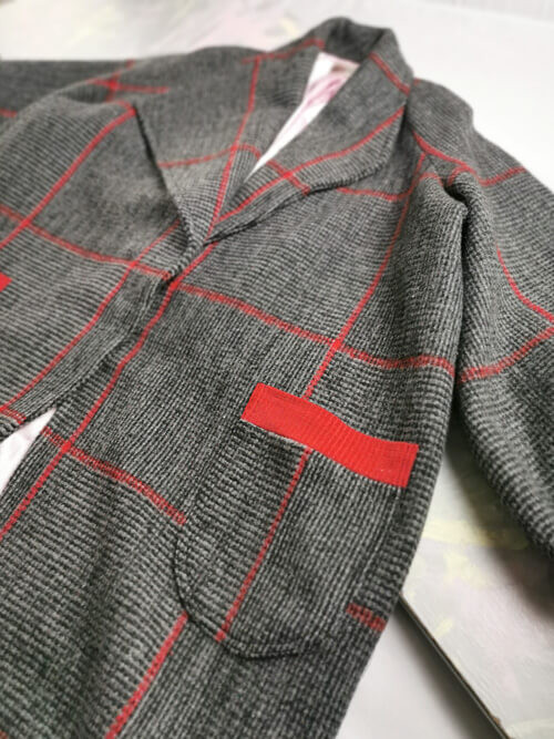 Flatlay of a handmade cocoon coat in grey and red check and a patch pocket.