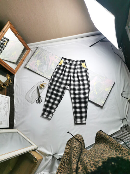 Shooting a flatlay image of a gingham pair of trousers.