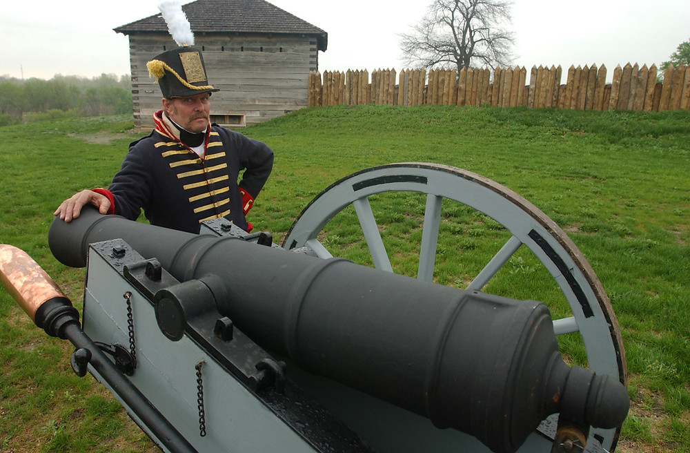 Soldier standing with cannon at Fort Meigs