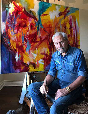 Robert Lombardi sitting in front of abstract painting with paintbrush in hand, The Lombardi Gallery, San Antonio Texas