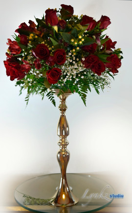 Tall centerpiece from red roses on golde