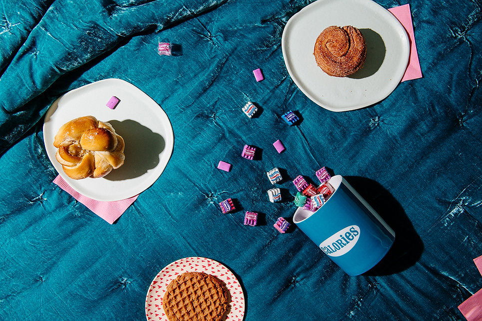 Breakfast in bed on a teal velvet comforter at an Airbnb in North Carolina. Popoves, peanut butter cookies and cinamon buns fill the frame with a Jonathan Adler cookie jar.