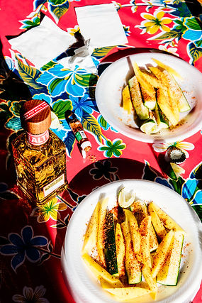 Mango and cucumber slices sprinkled with Tajin and served with Alto tequila on a vibrant oilcloth table.