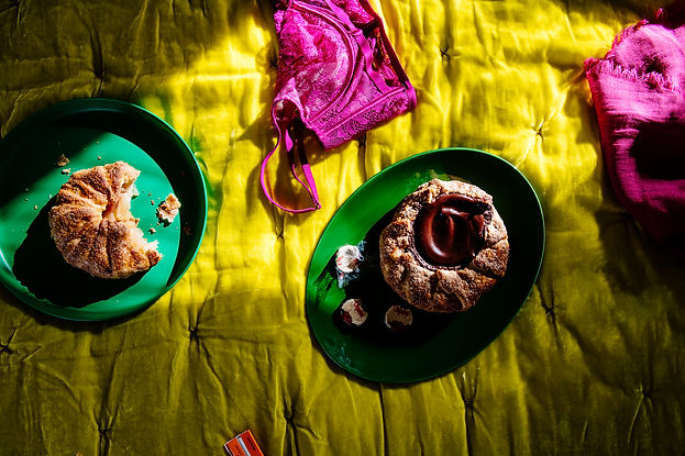 Chocolate galletes, apple hand pie and fuschia lingerie are sprinkled atop a chartruese velvet comforter at an Airbnb in North Carolina.