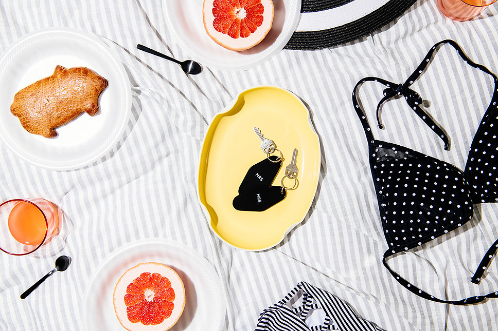 Two queer women enjoy breakfast in bed with grapefruit, mimosas and swimwear