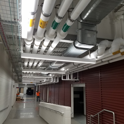 Overhead pipes and ducts are on full display with clear labels to encourage students about the building systems that surround them daily