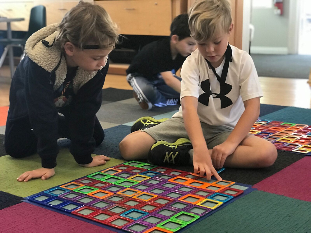 E.B. and G.A. discuss the measurement of their square made of squares.