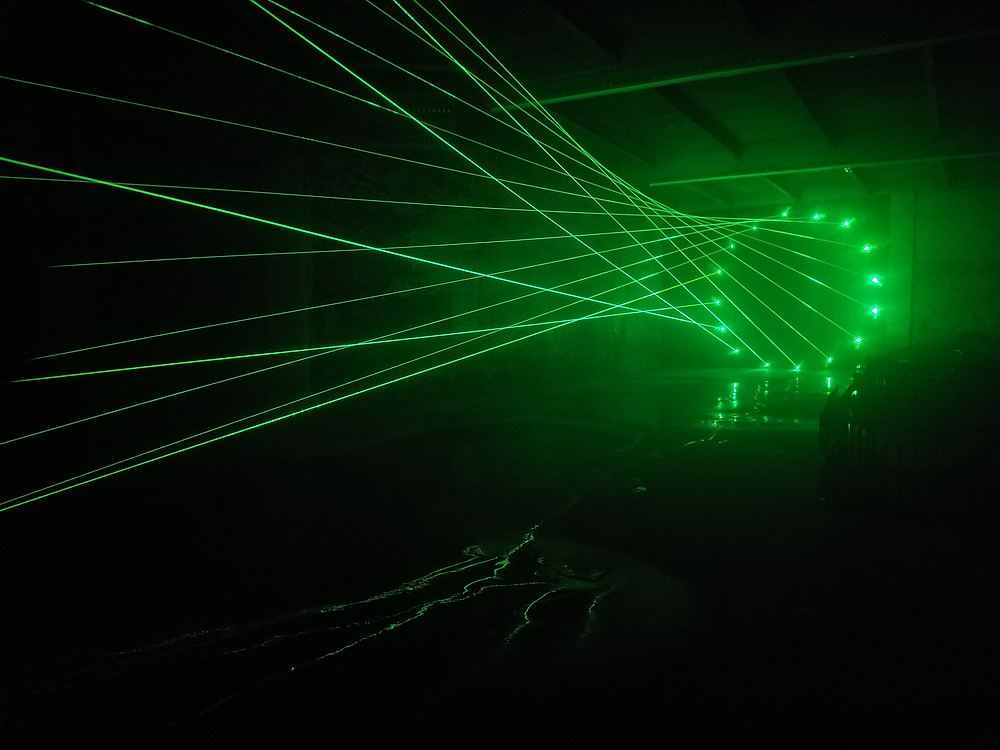 "Sixteen green laser beams stretch across the room, piercing through what the artist calls ""site-specific particulates, ambient extraterrestrial dust, and water."""
