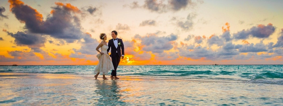 Prenup couple walking on beach at sunset